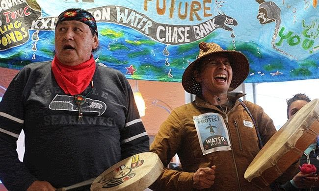A coalition of Indigenous leaders and other climate activists took over 12 JP Morgan Chase branches in Seattle, Washington, for a day of protest against the financing of tar sands projects