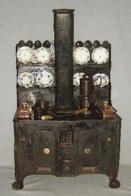 Grande et très belle cuisinière en métal noirci avec ses accessoires et sa cheminée, pieds griffes, deux bacs à eau chaude en cuivre avec boutons en porcelaine. Format : 75x42x26 cm. Pots et assiettes… - Lombrail-Teucquam - 27/03/2010