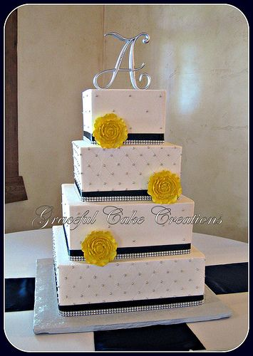Elegant White Wedding Cake with Navy Blue and Silver Bling Ribbon and Yellow Ranunculas