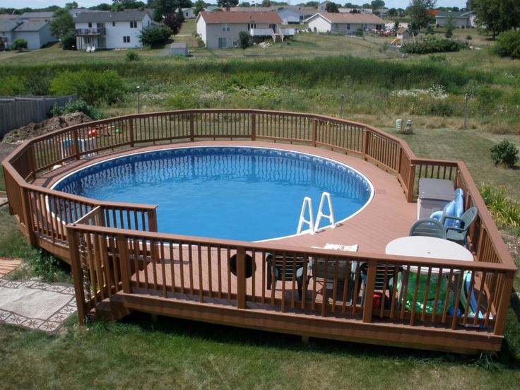 swimming pool wooden pool deck and railing also patio chairs around round above ground pool