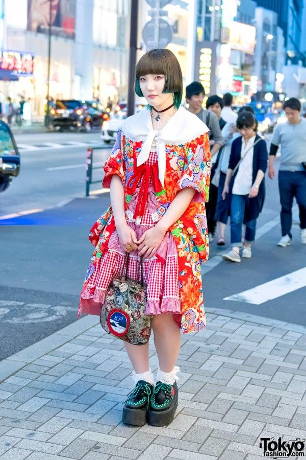 In addition to her asymmetrical green under dye bob hairstyle with sparkles, Hikaru's look here features a vintage kimono jacket over an Angelic Pretty dress and platform creepers with spider webs by the Japanese brand Yosuke. Accessories – some of which came from Mikansei Koenji – include a choker and a Kuroi Kagayaki purse.
