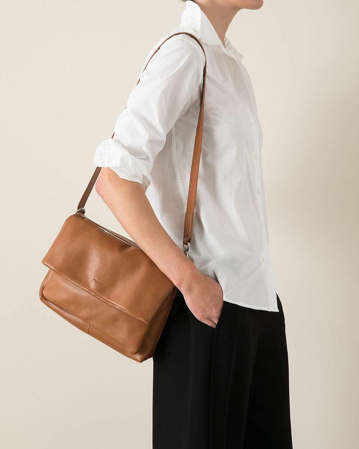 The Jemima Sling | Sleek, minimalist and designed with an innovative shoulder strap that adjusts to three different lengths for the ultimate in day‑to‑night versatility. Available in black pebble‑grain leather and caramel topgrain milled leather.
