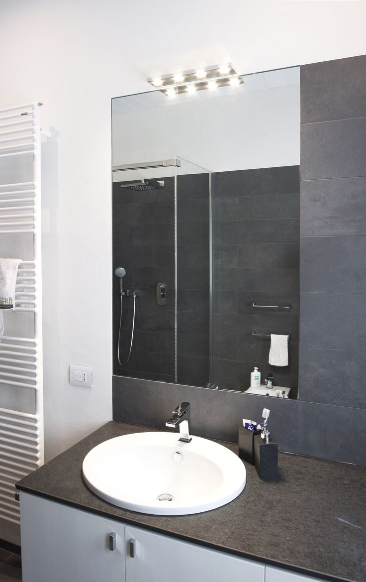 basin desk in whitened wood, black stone and a line of steel; a mirror cut into a wall