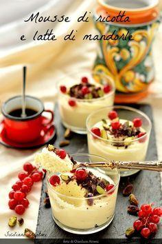 dalla Sicilia questa spuma di ricotta e latte di mandorla guarnita con pistacchio di Bronte, cioccolato e qualche bacca di ribes dal magnifico colore rosso