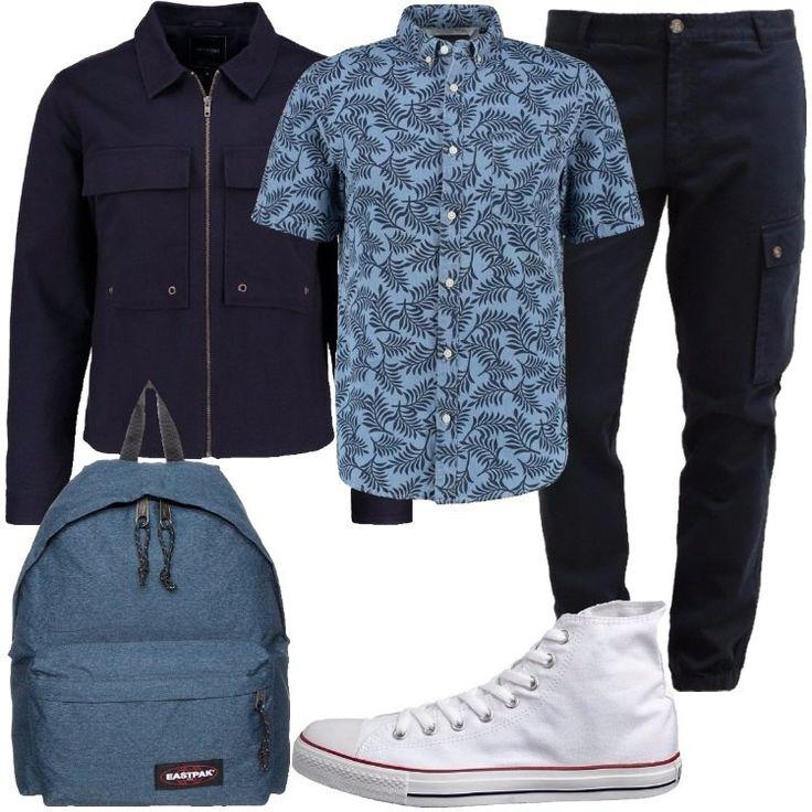 Camicia in cotone stampata, giacca in jeans con colletto classico e cerniera, pantaloni cargo a sigaretta. Ai piedi, scarpe in tela alte alla caviglia. Lo zaino in denim riprede il colore della camicia.