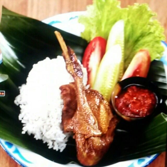 Fried duck with steamed rice, chili sauce and vegetables. Favorite street food for many Indonesian people