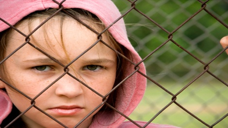 Child looking through a wire fence, Northern Ireland