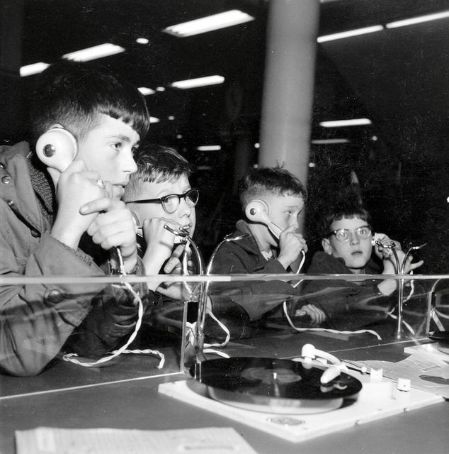 Nederlands: Jongens luisteren via een koptelefoon naar muziek in een platenwinkel. Nederland, november 1957.  English: Boys in a record shop. The Netherlands, location unknown, 1957.
