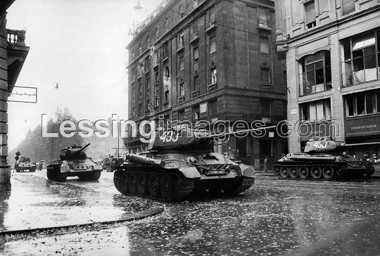 Heavy Soviet T 34/85 tanks protect a street crossing on the Pest side of Kossuth-Bridge. These heavy tanks proved too unwieldy for downtown battles and many were destroyed or captured by the insurgents. The visible markings on these tanks - 430, 433 and 442 - show they are Soviet tanks; the Hungarian army did not have such tanks. In the background: Hotel Astoria.   Townscape, Budapest, Hungary