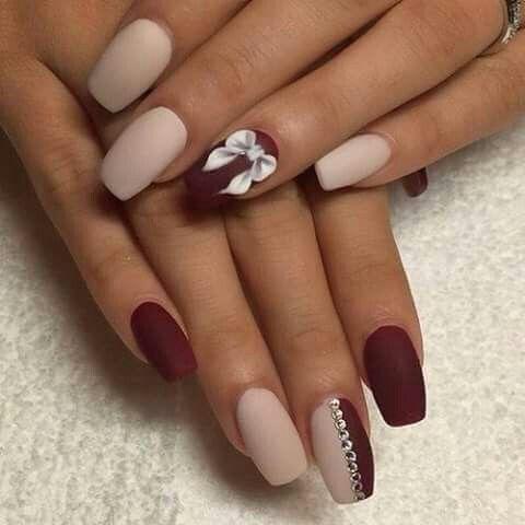 Punta escualeto en tonos piel y rojo adornando mano izquierda con un moño en bajo relieve y mano derecha con uña bicolor y tira de piedras