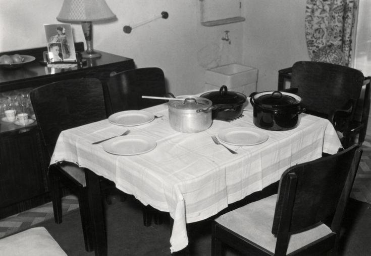 Eenvoudig gedekte eettafel met wit tafelkleed, borden, pannen en vorken, Haarlem, Nederland, 4 oktober 1951.