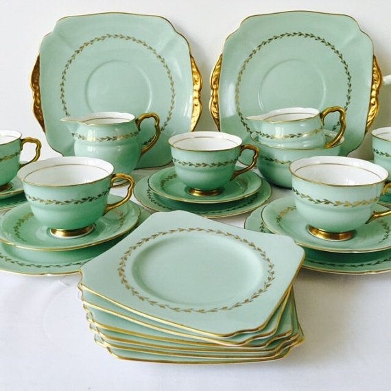A rich, striking fine bone china tea produced in 1938 by Doulton & Co Ltd of Nile Street, Burslem, Staffordshire, better known simply as Royal Doulton. The set is made up of 5 teacups, 5 saucers, 5 square tea plates, 5 slightly larger, round tea plates, 2 milk jugs, 1 sugar bowl and 2 matching cake/serving plates, all decorated in a fabulous blue-green adorned with the best quality burnished gold details and a simple gilt band of stylised leaves. The pattern is H4612, dating specifically to…