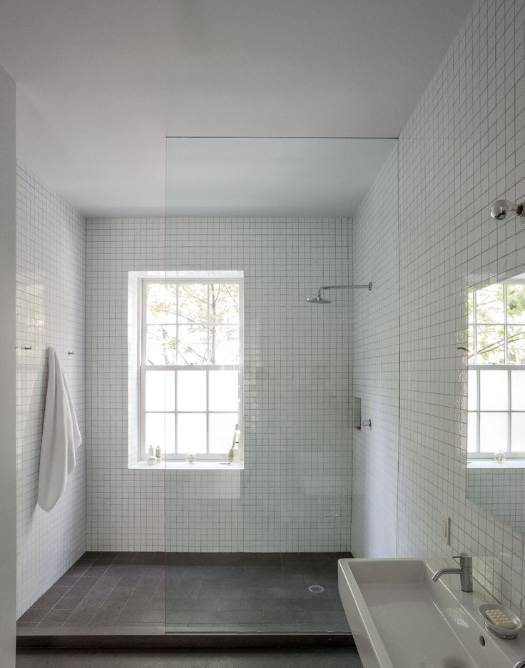 Simple curtainless shower in classic black and white, with a window. No threshold would be even better!