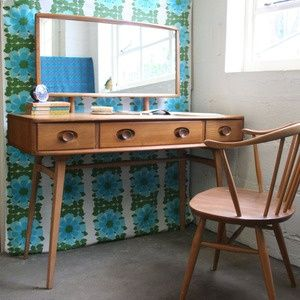 The elegant lines of this dressing table and chair are so elegant and the warm wood tones are complemented by the retro wallpaper. I am coveting this combo.