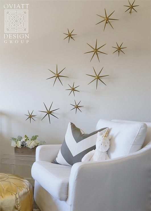 White and gold nursery boasts a white slipcovered glider lined with a gray chevron pillow as well ...