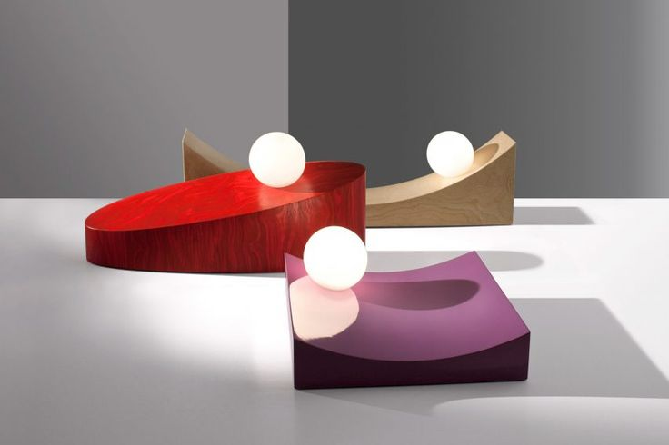 The lights appear to have been caught in the middle of sliding or rolling down wooden plinths of various shapes and sizes.