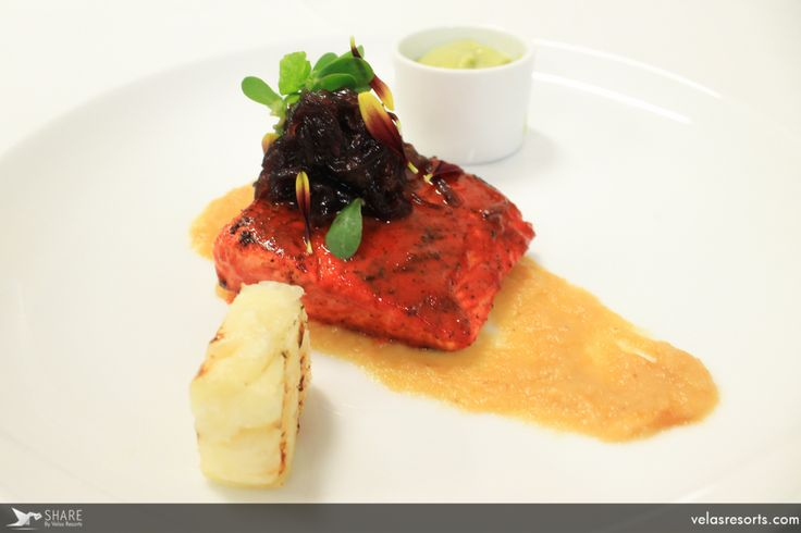 Fire-roasted pastor-style salmon seasoned with annatto, with caramelized onion, butter and cilantro salad.