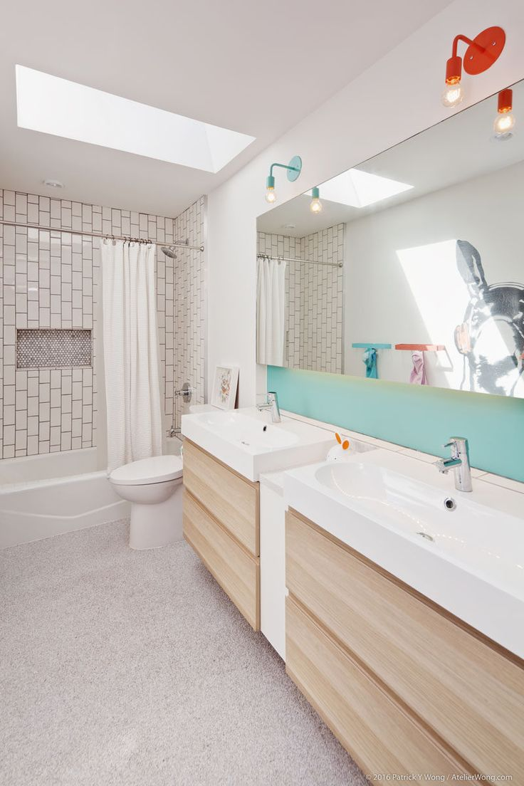 This modern kids bathroom has a skylight, colorful lamps, backsplash and towel racks, and a fun animal mural on the wall. #KidsBathroom #BathroomDesign #ModernBathroom