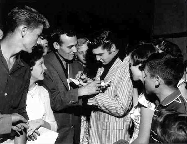 Elvis and Carl Perkins exchanging autographs. On May 1, 1956 Elvis made a surprise visit to the Overton Park Shell in Memphis. Johnny Cash, Carl Perkins, Roy Orbison and Warren Smith were performing there but Elvis did not perform.  Photo © Alfred Wertheimer All rights reserved
