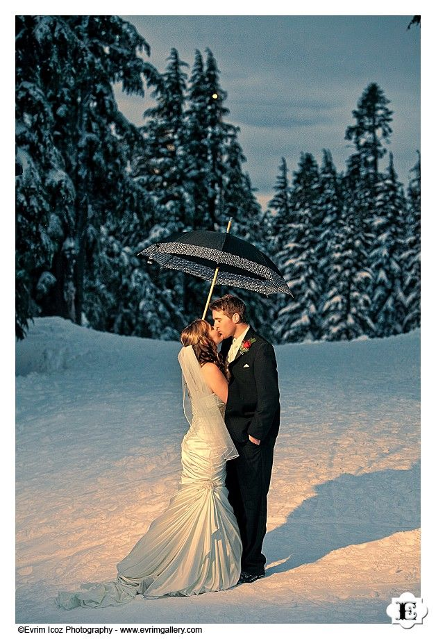 Bride and groom share a kiss under an umbrella at this Timberline Lodge wedding