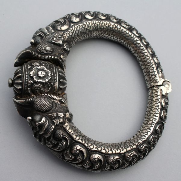 A 19th century makara head bracelet from Madras, India. Worked in the most exquisite, tiny silver repousse. The makara's have waves on their backs, tiny scales on their bellies, and hold a magical jewel in their jaws.