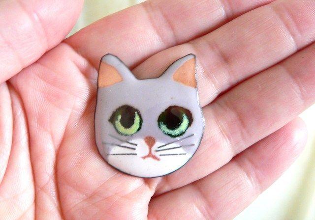 パールグレイと銅白の釉薬で焼いた猫です。瞳はグリーンです。写真は、まだ金具をつけていない状態です。 裏に回転ピンをつけてブローチになります。 また、着物の帯止め金具をつけることもできます。ご希望の方はメッセージにてお知らせください。