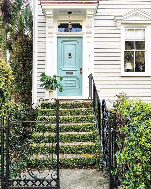 Ivy-covered stairs pair perfectly with a turquoise front door and paneled exterior!