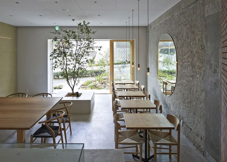 A large circular mirror reflects a tree planted in the centre of this Osaka cafe.