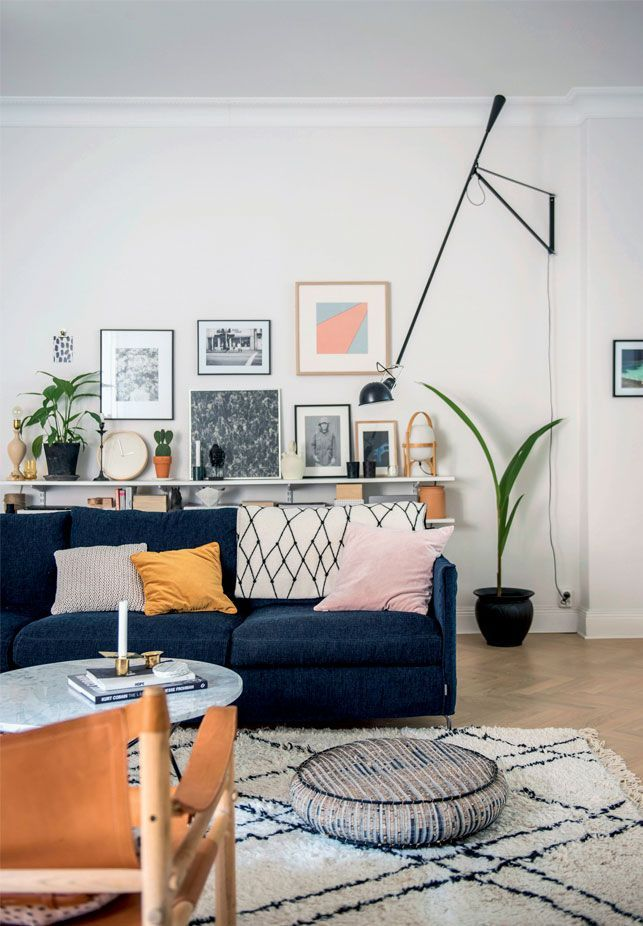 Amazing wall art gallery, full of color. Dark blue couch, perfectly patterned rug and floor cushion.
