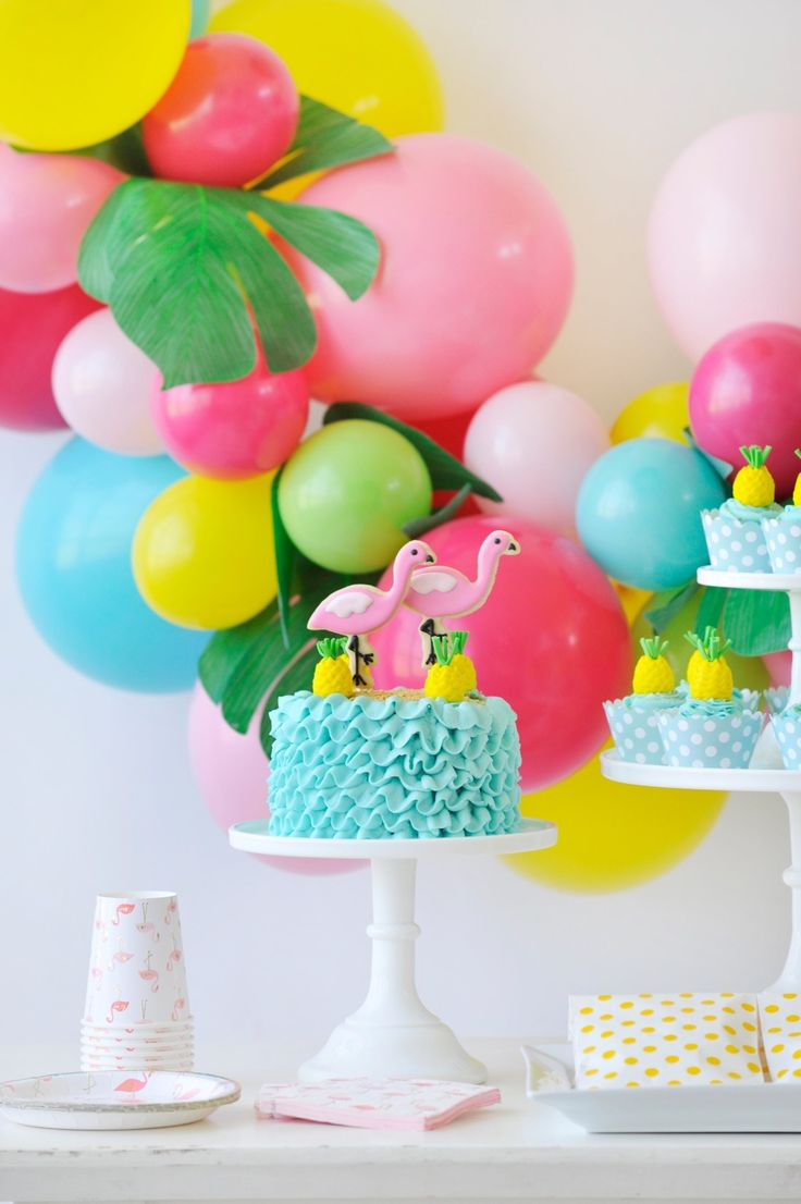 This colorful dessert table with a combination of turquoise, lime green, yellow and shades of pink creates a tropical paradise. Flamingo Party styling by Happy Wish Company. Photography by Tammy Hughes Photography. Stationery by Minted artist, Laura Hankins.