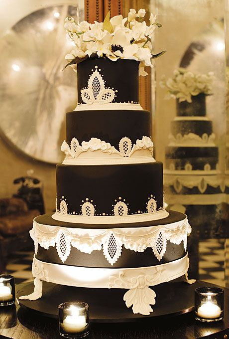 Brides.com: 22 Wedding Cakes for Dark, Modern Color Palettes. A Formal, Black and White Wedding Cake. Ron Ben-Israel Cakes created this opulent, four-tier masterpiece for a formal wedding. We can see why—the white, lacy detailing and lush flower topper remind us of the fanciest wedding dresses.  See more black wedding cakes.