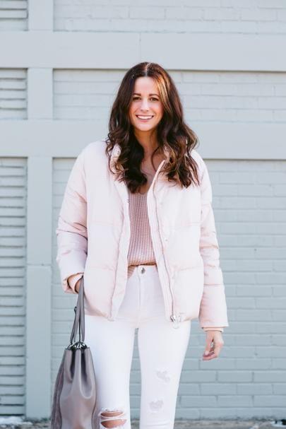 Amanda Miller wearing a light pink puffer jacket and light pink V neck sweater
