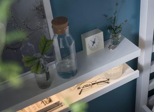Ein Ablagetisch aus zwei MOSSLANDA Bilderleisten in Weiß, darauf sind ein Wecker, Gläser mit Zweigen und eine Karaffe mit Stöpse zu sehen.