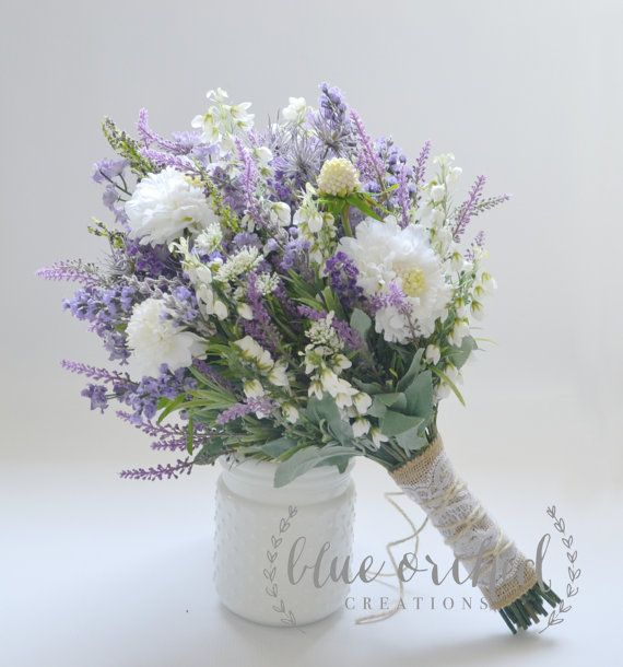 This wildflower bouquet features lavender, purple wildflowers, some white wildflowers, and light blue accents. The shabby chic design has a