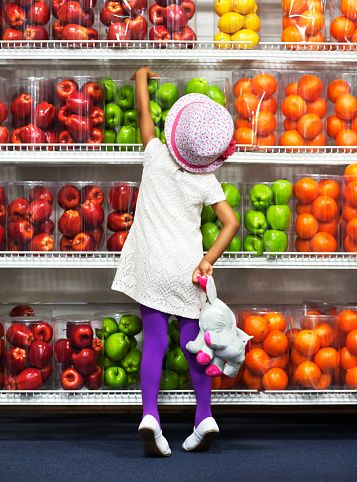 Stock Photo : Girl reaching for apple in supermarket