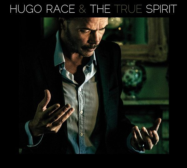 The Spirit (Glitterhouse). Che piacere ritornare nelle grotte di suono di Hugo Race e dei True Spirit e ritrovare intatte quelle scure e cangianti stalattiti, grondanti sonorità dub e riverberi noir, oscurità e freschezza, sensualità e fascino ancestrali. Lo Spirito è un suono caldo ma rinfrescante, un flusso sonico in cui la voce fumosa di Hugo (un Mark Lanegan in giacca e cravatta) ti guida tra post punk, psichedelia, blues primordiale, elettronica dub analogica da vero maestro, da cui è…
