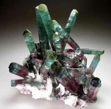 Tourmaline. Comes in many diferent colors. Pink, red (rubellite), violet, brownish, dark brown, yellow (dravite), blue (indocolite), deep black (schorl), green (verdelite) also green, innen to pink to red (watermelon), colorless (albaite) Blue linked to Libra, green to Capricorn, pink and red to Scorpio. Symbolizes wealth friendship and love.