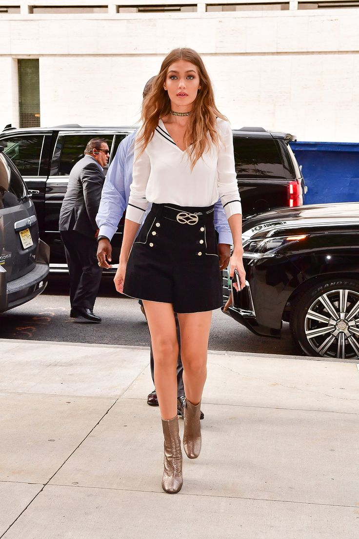 Keeping up with the nautical theme of her Tommy Hilfiger collab, Hadid wears a sailor-esque blouse, belted high-waisted shorts with button details, metallic boots and a choker to her Tommy x Gigi press conference in NYC.