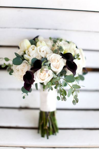 The deep dark purple mini calla lilies give this wedding bouquet an autumn feel. It's a great contrast to the cream roses, tulips and eucalyptus greens.