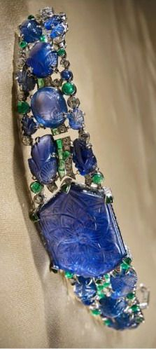 carved sapphire bandeau / bracelet    Mrs. Veronica Hearst Bracelet / Bandeau 1927  Beautifully engraved, this piece boasts a hexagonal 59.38 carat sapphire,  Complimented by smaller leaf-shaped oval sapphires and sapphire cabochons, emerald cabochons and calibre-cut emeralds. Mrs. Veronica Hearst, wife of American press baron William Randolph Hearst and she purchased this piece in 1927.
