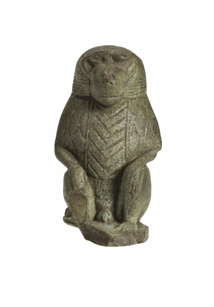 Amulet in dark green-brown faience in the form of an ape squatting: Ancient Egyptian, from Benha, Late Period.