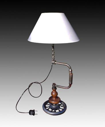 Lampe de table, composée d'une chignole ancienne et son forêt à bois, montée sur un volant de machine à coudre.  L'ensemble est vernis, aspect satiné. Elle est équipée d - 17594538