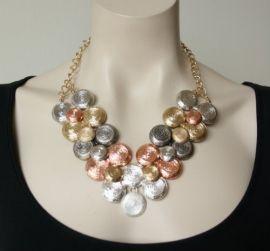 Een prachtige opvallende statement halsketting met bewerkte metalen discs in goud, zilver met roze goud kleurige metaal.€ 34,95