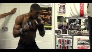 Anthony Joshua trains on the heavy bag overseen by coach Tony Sims