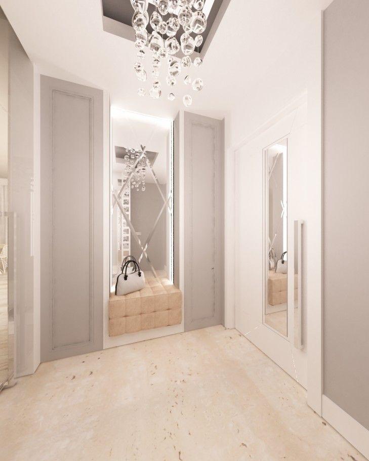 Projekt wnętrza holu w rezydencji w stylu nowoczesnym. Niewielkie pomieszczenie wykończone w tonacji bieli i szarości zdobią sztukaterie na ścianach i ozdobne fazowane lustro.