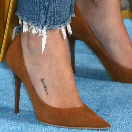 """Selena Gomez's tattoo on the outside of her right foot that reads """"Sunshine"""" in a simple black text and was inspired by her """"Nana,"""" maternal grandmother Debbie Jean Gibson."""
