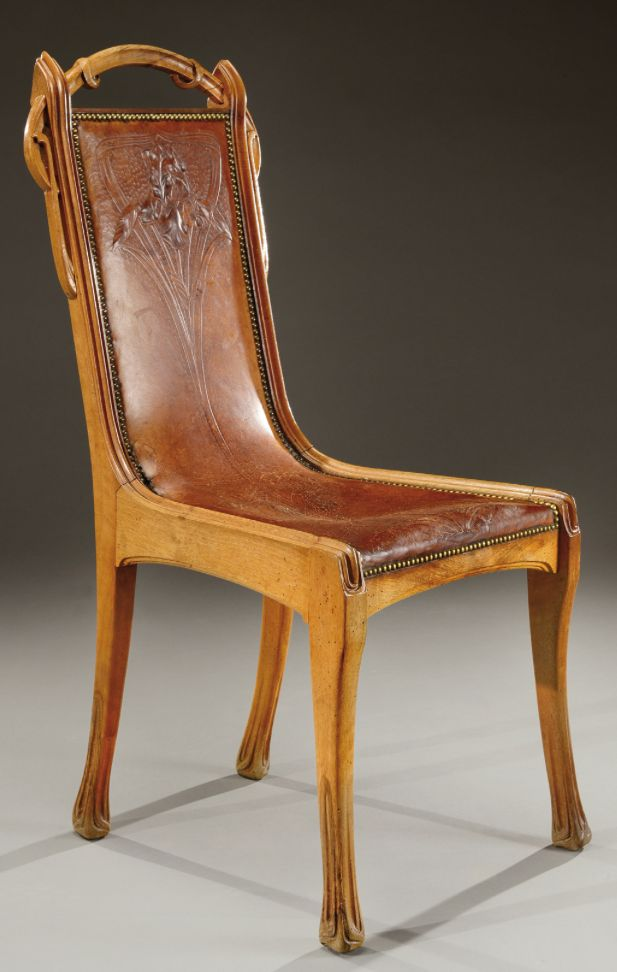 EUGENE GAILLARD rare Art Nouveau carved walnut chair with a leather seat hand tooled with an iris flower. Circa 1900.