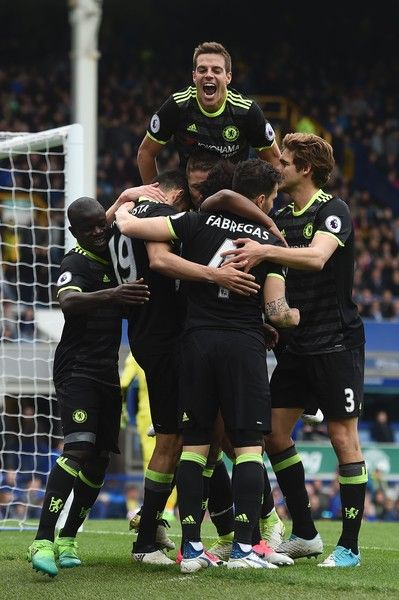 Chelsea's Spanish defender Cesar Azpilicueta (top C) jumps onto the celebration after Chelsea's Brazilian midfielder Willian scored their third goal during the English Premier League football match between Everton and Chelsea at Goodison Park in Liverpool, north west England on April 30, 2017. / AFP PHOTO / PAUL ELLIS / RESTRICTED TO EDITORIAL USE. No use with unauthorized audio, video, data, fixture lists, club/league logos or 'live' services. Online in-match use limited to 75 images, no…