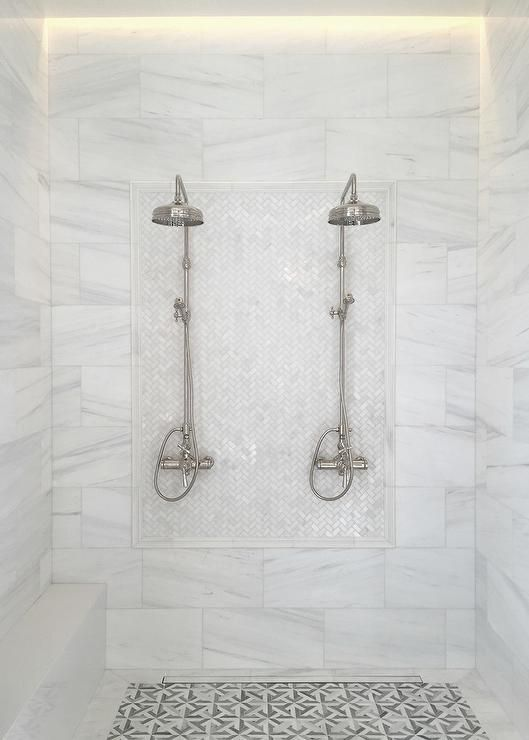 Side by side his and her rain shower heads are mounted to white marble herringbone accent tiles surrounded by large white marble stacked tiles framing a slim marble bench and complementing gray geometric floor tiles.