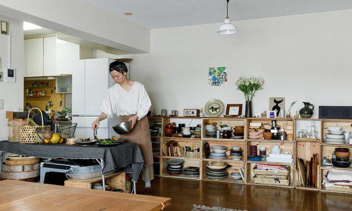 部屋を決める基準 東京都世田谷区の住宅街にある、12階建てのマンション。ここに昨年引っ越してきたのは、「minokamo」という名義で料理と写真を生業とする長尾明子さん。ご主人との二人暮らしだ。「自宅で料理の撮影もしますし、昔から仲間を招いて宴を開くのが好きなので、広いリビングは絶対条件だったんです。キッチンは本当は対面式がよかったけれど、広いテラスと眺望が決め手になりました」。 「minokamo」は、長尾さんの出身地・岐阜県美濃加茂市から取ったもの。郷土料理をアレンジしたレシピ提案や食を通じてのイベントなど、仕事は多岐にわたる。 上京した頃からよく自宅に友人を招くようになり、その友人が実家などから持ち寄る郷土色豊かな食材を料理するのが長尾さんの楽しみだったという。「私はみんなで食卓を囲んでごはんを食べるのが大好きなだけ。その延長線が今の仕事につながっているんです」。テラスは、テーブルセットとハンモックを置いても、まだまだ余裕がある広さ。 玄関から見たリビング。敷いてあるラグはモロッコで手に入れたもの。右手にテラスが広がり、左手前がキッチンにつながる。…